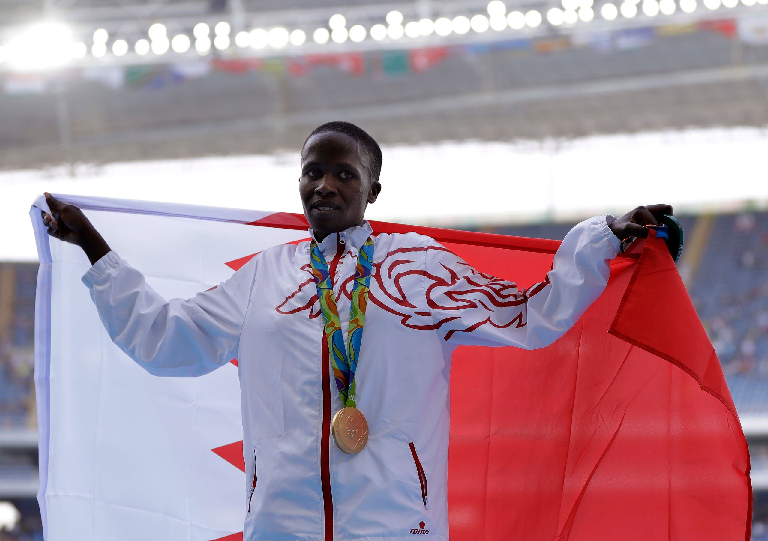Bahrain's gold medal winner Ruth Jebet holds the Bahrain flag during the ceremony for the women's 3000-meter steeplechase final during the athletics competitions of the 2016 Summer Olympics at the Olympic stadium in Rio de Janeiro, Brazil, Monday, Aug. 15, 2016. (AP