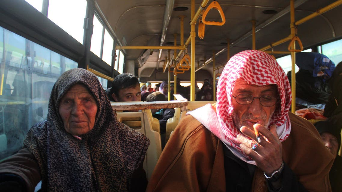 Residents from the mostly Shiite Syrian villages of Kafraya and Fuaa, which are besieged by opposition fighters, wait in a bus to get a green light from the rebels to cross into a government controlled area in the province of Aleppo, on December 20, 2016. Some 750 people had been evacuated in parallel from the embattled city of Aleppo, from Fuaa and Kafraya, two Shiite-majority villages in northwest Syria besieged by rebels, as part of the deal to evacuate civilians. afp