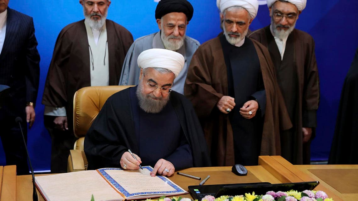 """In this photo released by official website of the office of the Iranian Presidency, President Hassan Rouhani signs the document of Iran's """"Charter of Citizenship Rights."""" in a conference called """"Constitution and the Nation's Rights."""" in Tehran, Iran, Monday, Dec. 19, 2016."""