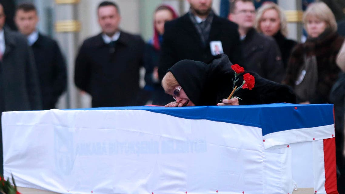 Marina Davydova Karlova, widow of late Russian Ambassador to Turkey Andrei Karlov, reacts in front of his coffin, during a ceremonial farewell with full state honors on the tarmac of Ankara's Esenboga Airport on December 20, 2016, before the coffin is transported on a Russian plane for Moscow. (AFP)