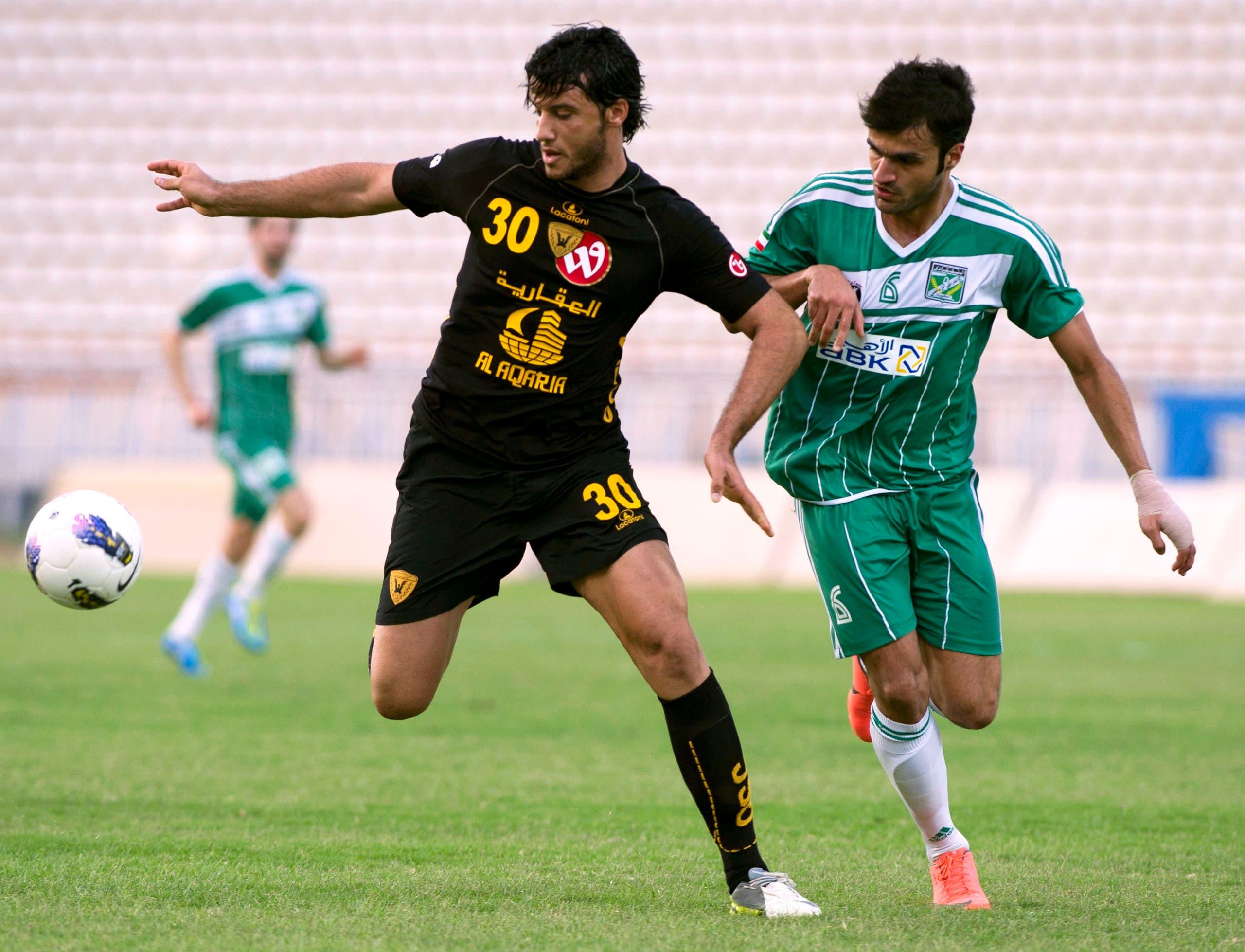 Al Qadsia's Omar Al Somah (L) challenges Al Arabi's Ahmed Abdulgafor during their Premier League soccer match in Kuwait City May 5, 2012. REUTERS