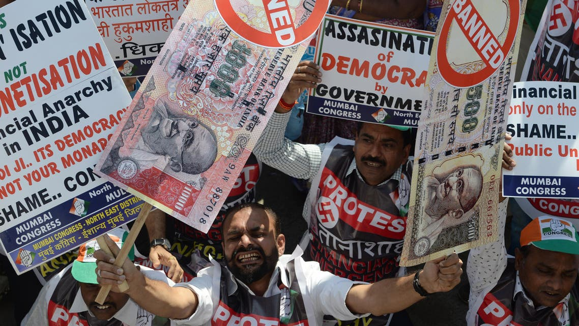 An Indian protestor holds placards of banned 500 and 1000 rupee notes during a protest against demonetization, in Mumbai on November 28, 2016. (AFP)
