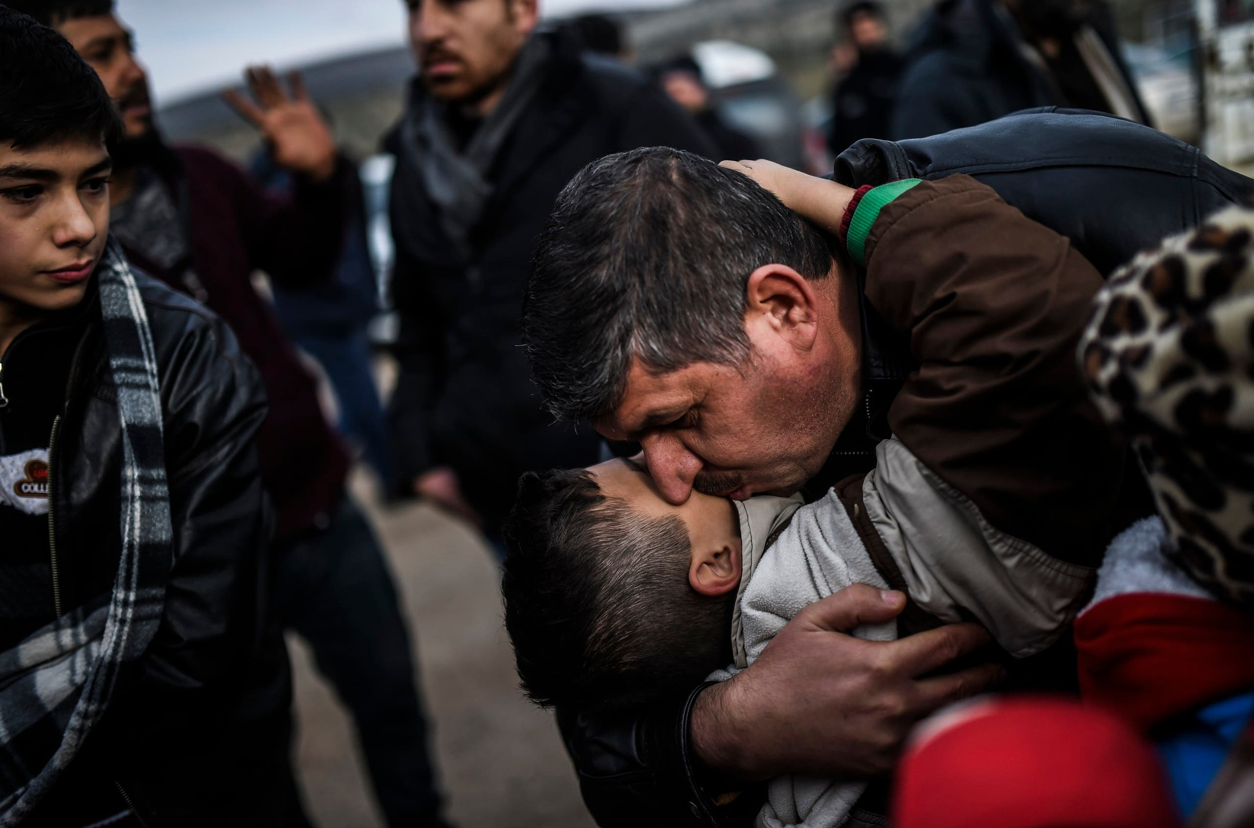 Syrian father Ali embraces one of his children, Zeyn, upon their arrival from the Syrian city of Idlib to the Turkish crossing gate of Cilvegozu in Reyhanli in Hatay near the Syrian border on December 17, 2016. (AFP)