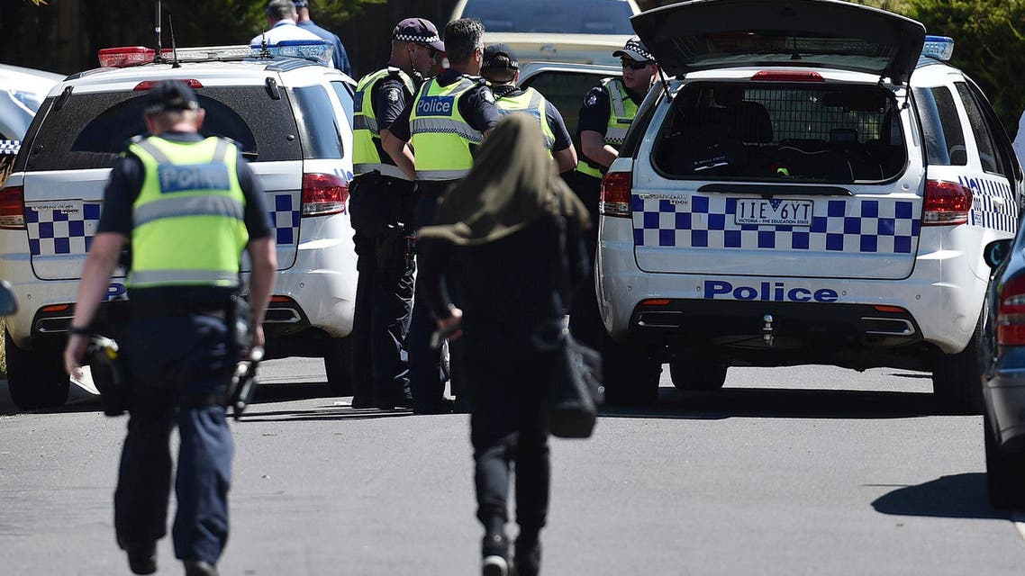 Police accompany a woman as they attend the scene where a house was raided at Meadow Heights in Melbourne, Australia, Friday, Dec. 23, 2016. (AP)