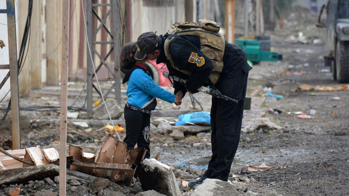A member of Iraqi special forces kisses a child in the neighborhood of al-Barid east of Mosul on December 18, 2016 during their ongoing operation against ISIS to militants wrest back the city. (AFP)