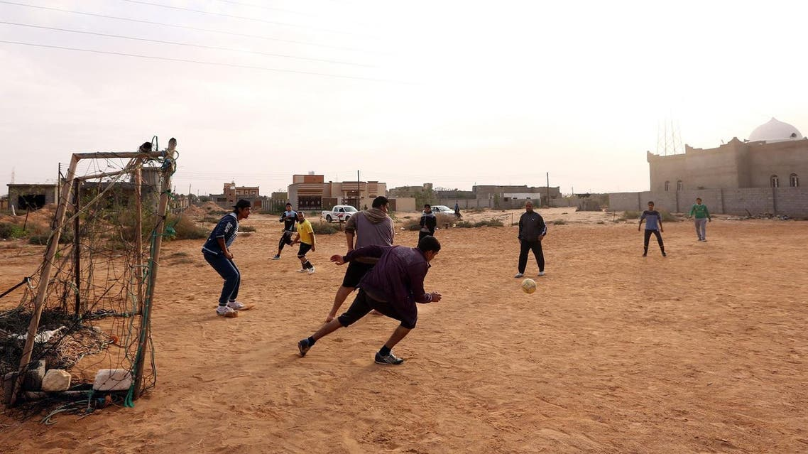 Young people from the city of Sirte, 450 kilometres east of the Libyan capital Tripoli, play football after returning to the outskirts of the city. (AFP)