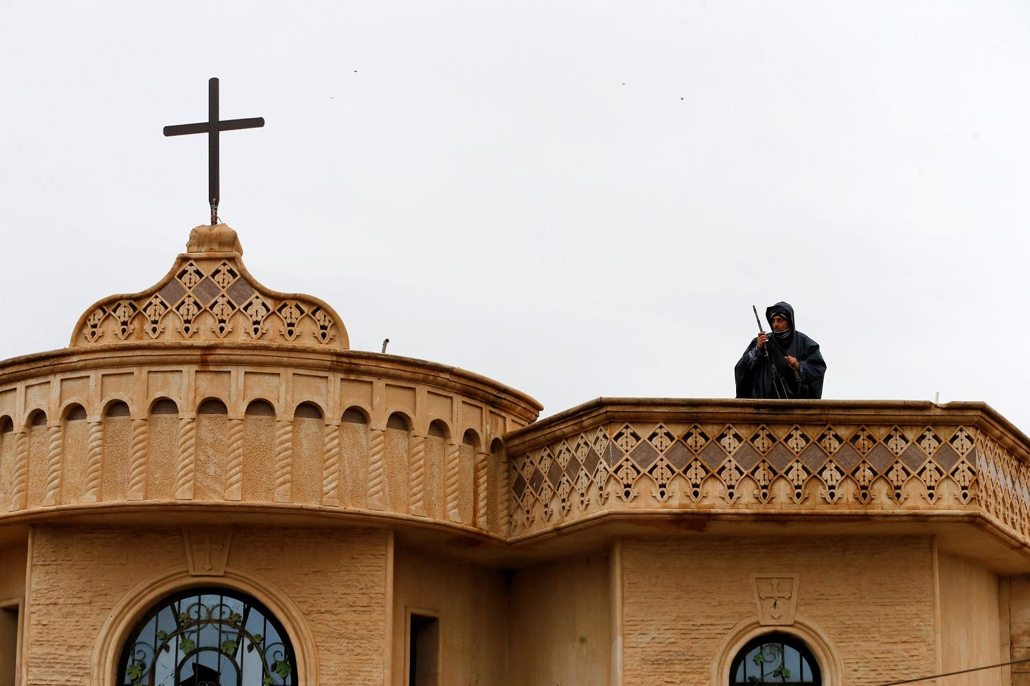 A security member stands guards on the top of church during a mass on Christmas Eve at the Mar Shemoni church in the town of Bartella east of Mosul. (Reuters)