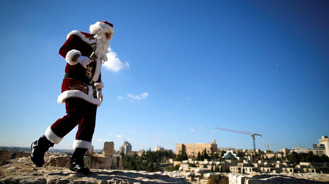 Kassissieh wears a Santa Claus costume as he walks atop Jerusalem's Old City walls. (Reuters)