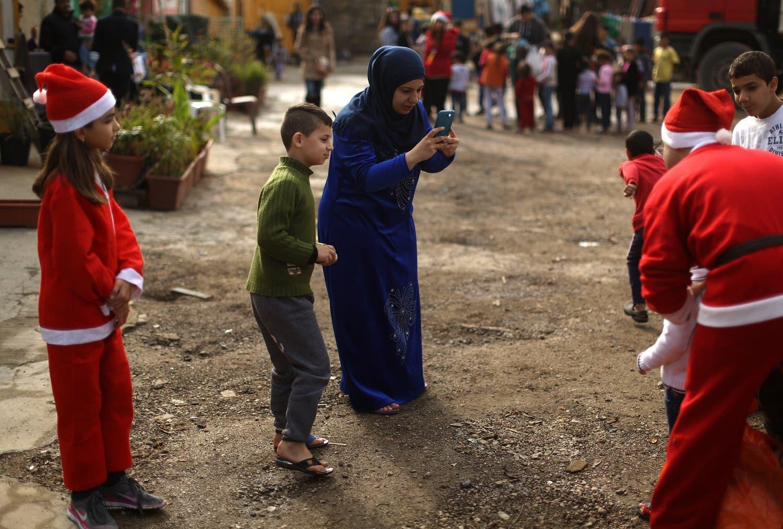 حلب سے تعلق رکھنے والی ایک شامی مہاجر خاتون اپنے بیٹے کی سانتا کلاز کا روپ دھارنے والے لبنانی رضاکار کے ساتھ تصویر بنا رہی ہے۔