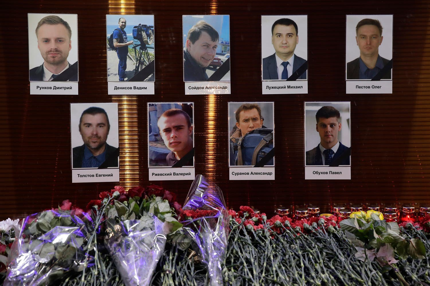 Flower tributes in front of portraits of Russian TV journalists who were aboard the crashes military plane. (AP)