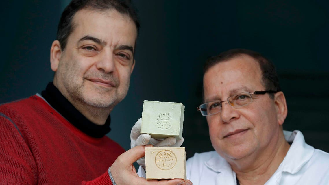 Franco-Syrian Samir Constantini (L), CEO of Alepia brand, and Syrian master soapmaker Hassan Harastani, who fled Syria and decided to produce Aleppo soap on French soil, pose December 22, 2016, holding bars of soap at the company's factory in Santeny, near Paris. Picture December 22, 2016. (Reuters)
