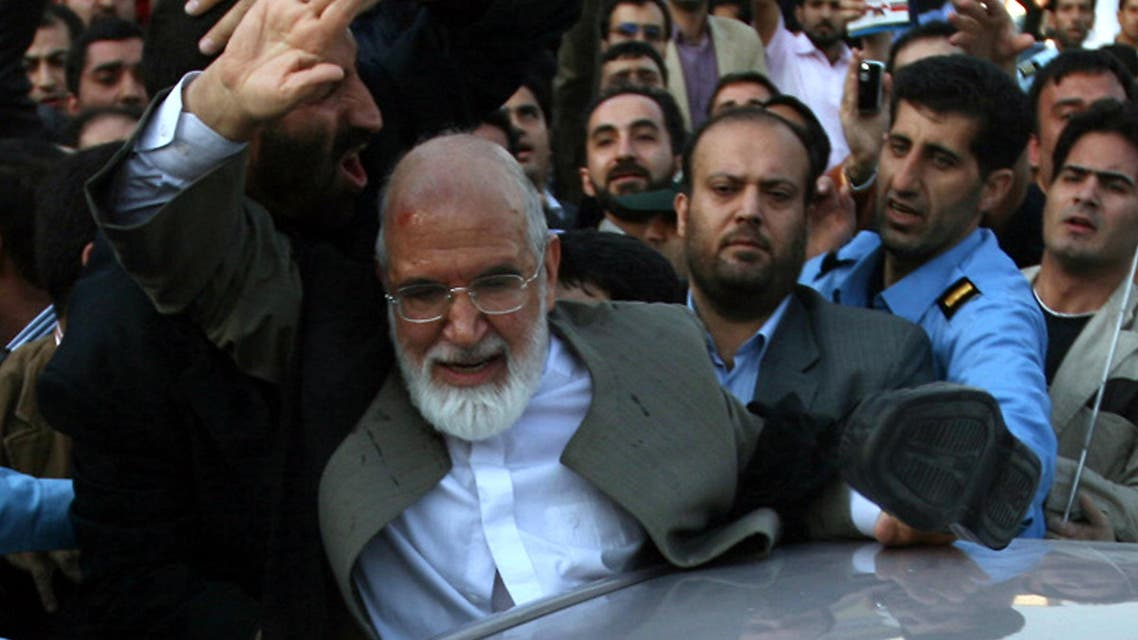 This picture dated October 23, 2009 shows Iranian opposition leader Mehdi Karroubi raising his hand after a shoe hit him in the head and his turban fell off as he was leaving the 16th annual press fair in Tehran. (AFP)