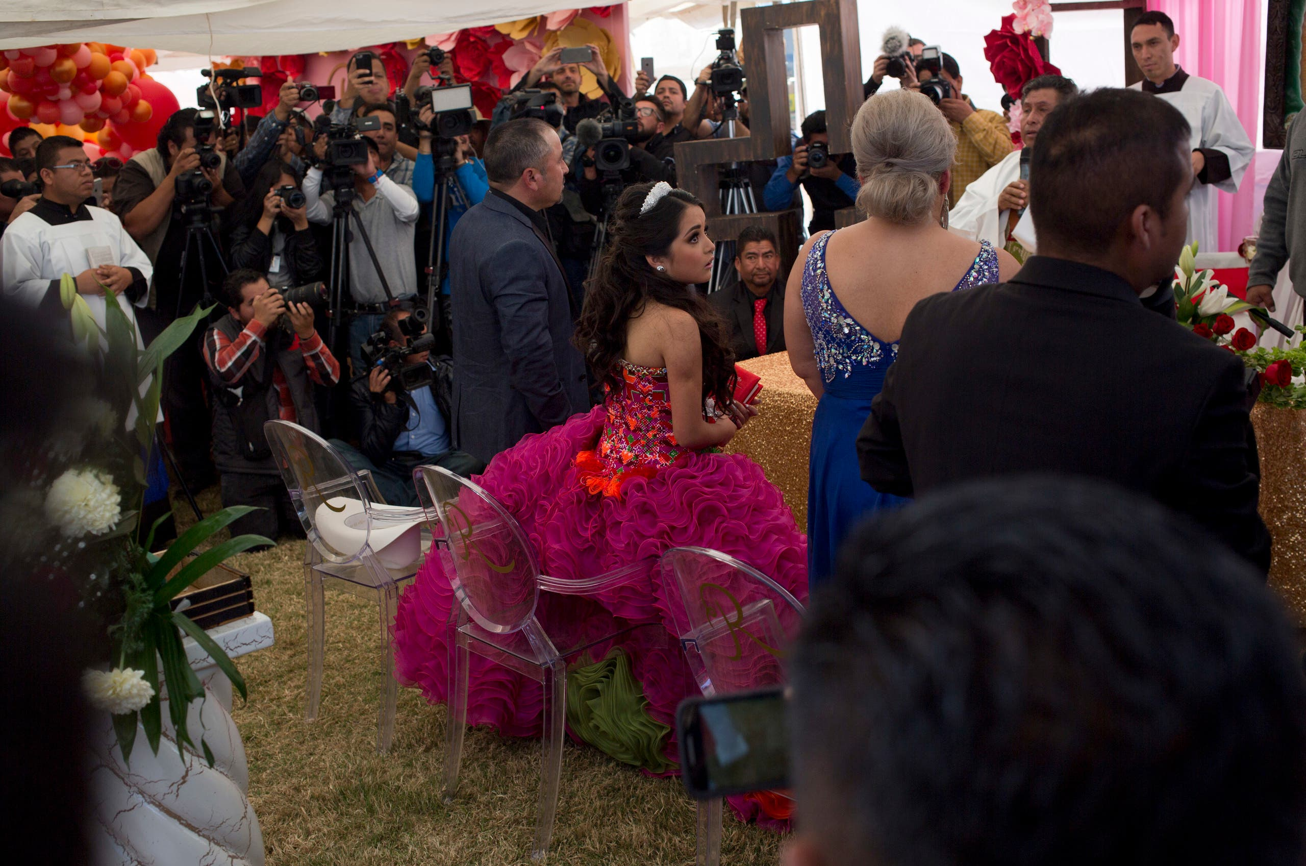 Rubi Ibarra looks at her mother Anaelda as journalists struggle to get images during a Mass as part of Rubi's down-home 15th birthday party in the village of La Joya, San Luis Potosi State, Mexico, Monday, Dec. 26, 2016. AP