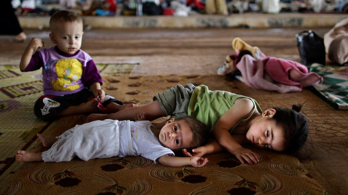 Syrian children, who fled their home with their family due to fighting between the Syrian army and the rebels, lie on the ground, while they and others take refuge at the Bab Al-Salameh border crossing, in hopes of entering one of the refugee camps in Turkey, near the Syrian town of Azaz, Sunday, Aug. 26, 2012.