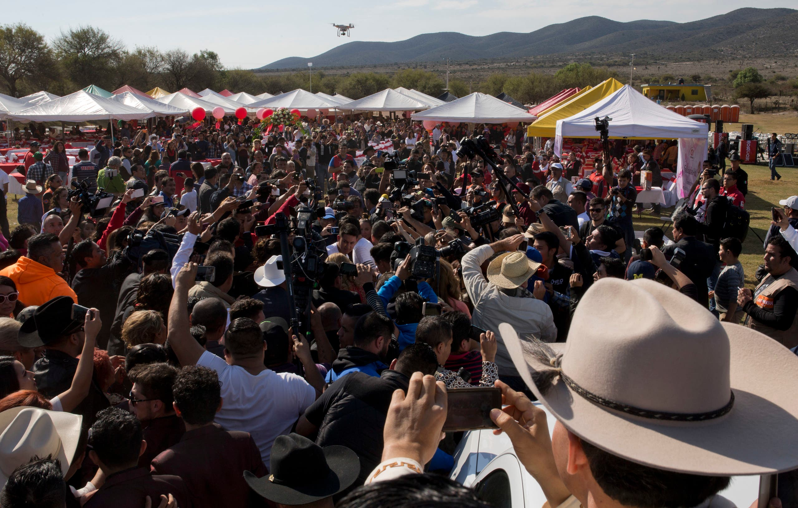 Rubi Ibarra, not seen, arrives at the site of a Mass that is part of her down-home 15th birthday party, surrounded by a horde of journalists and a drone flying overhead, in the village of La Joya, San Luis Potosi State, Mexico, Monday, Dec. 26, 2016. AP