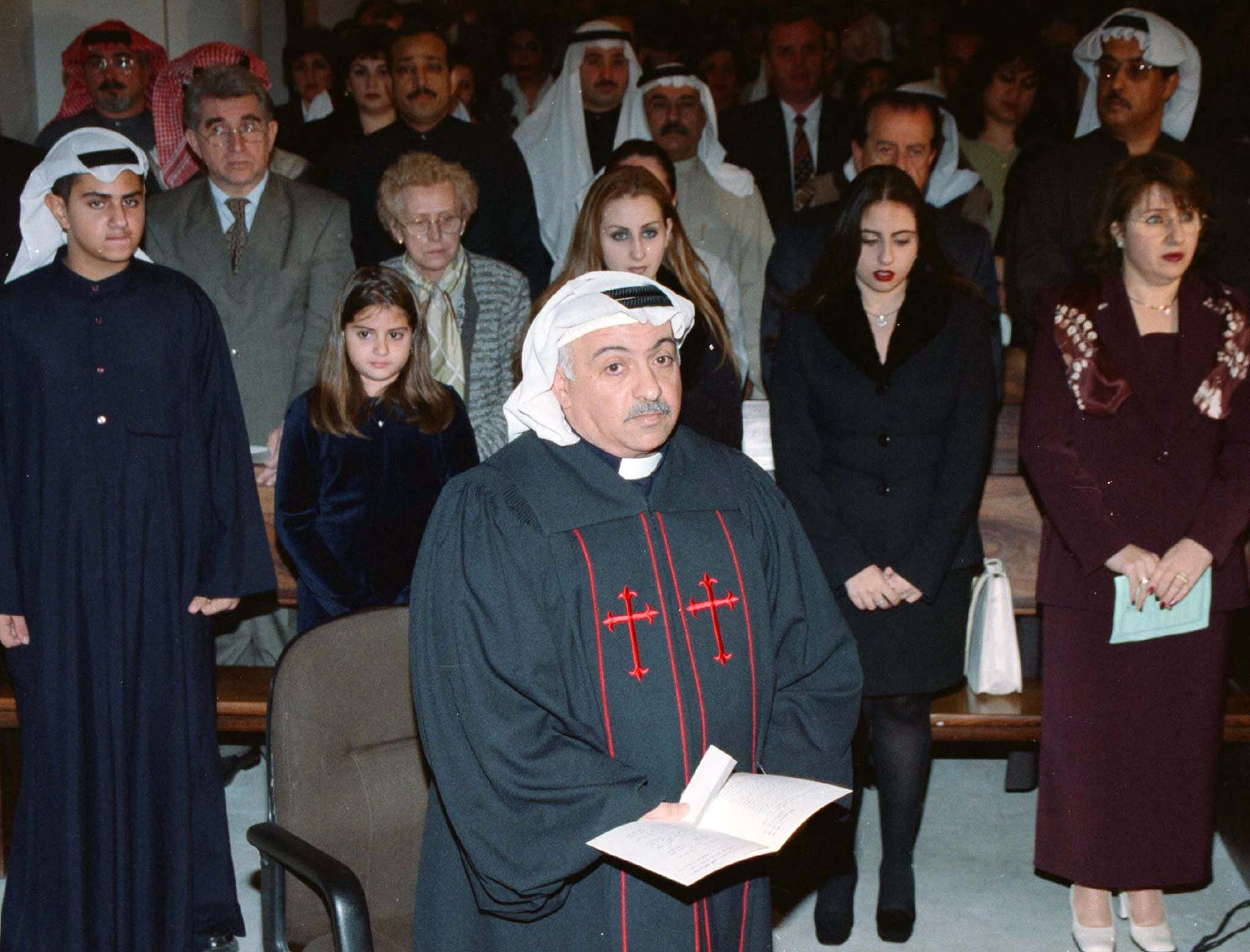 Kuwaiti citizen Emmanuel Benjamen al-Gharib (C) prays on January 8, 1999 while his wife and children stand in the church pews behind him. (Reuters)