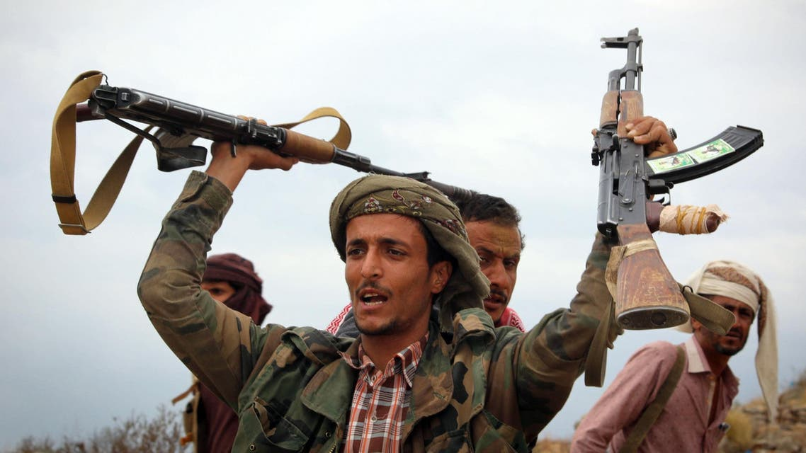 A Yemeni tribesman from the Popular Resistance Committee, supporting forces loyal to Yemen's Saudi-backed President Abedrabbo Mansour Hadi, raises weapons during clashes with Shiite-Huthi rebels in the country's third-city of Taez on December 19, 2016.  Ahmad AL-BASHA / AFP