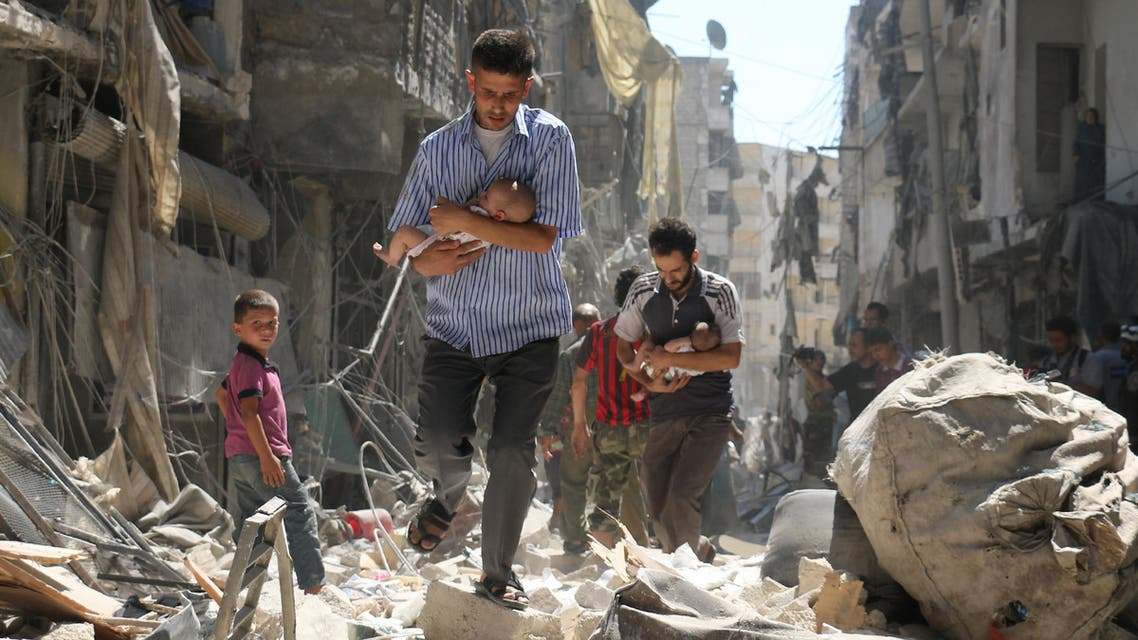 Syrian men carrying babies make their way through the rubble of destroyed buildings following a reported air strike on the rebel-held Salihin neighbourhood of the northern city of Aleppo, on September 11, 2016. (AFP)