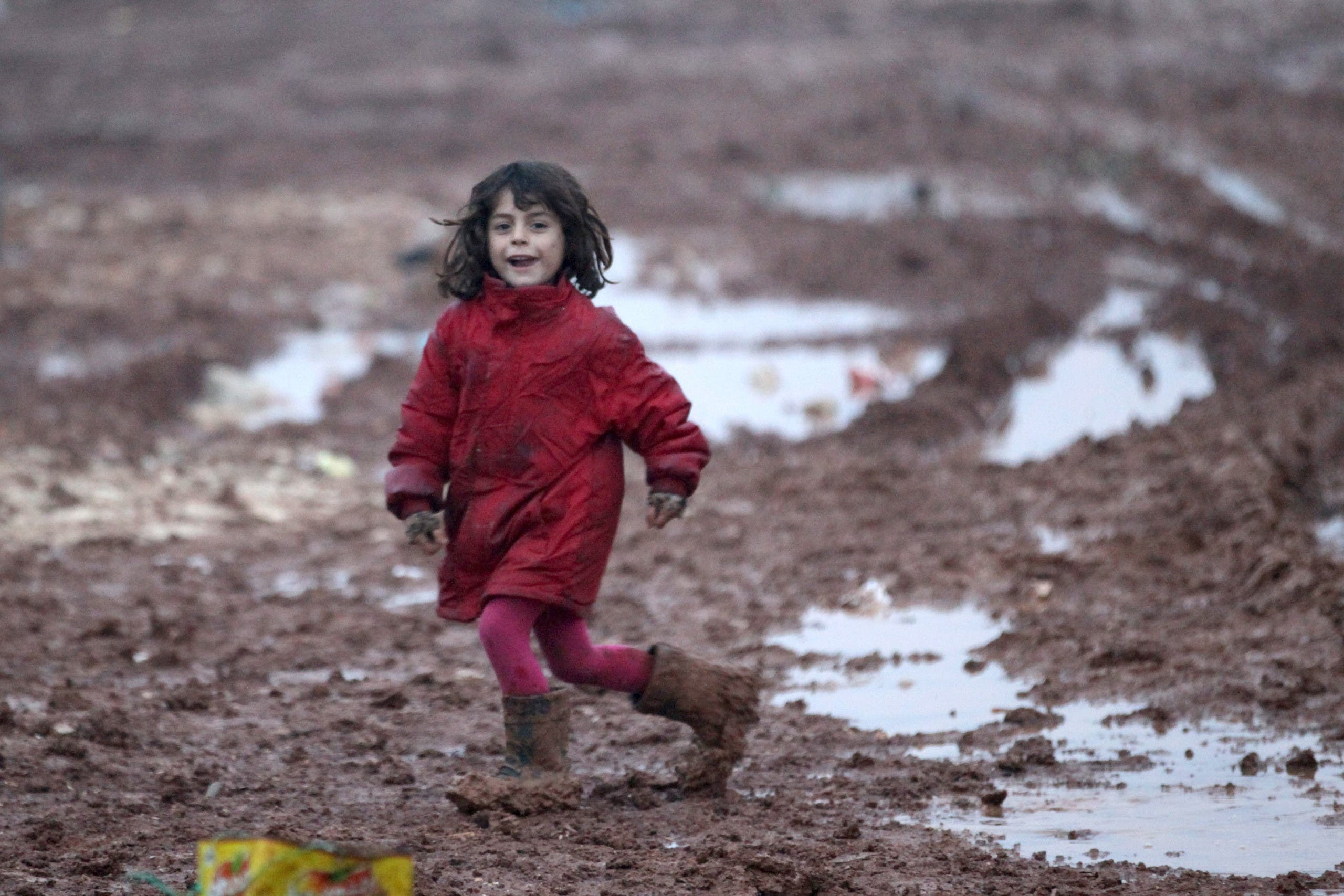 An internally displaced Syrian girl runs through mud in the Bab Al-Salam refugee camp, near the Syrian-Turkish border, northern Aleppo province, Syria December 26, 2016. REUTERS/Khalil Ashawi