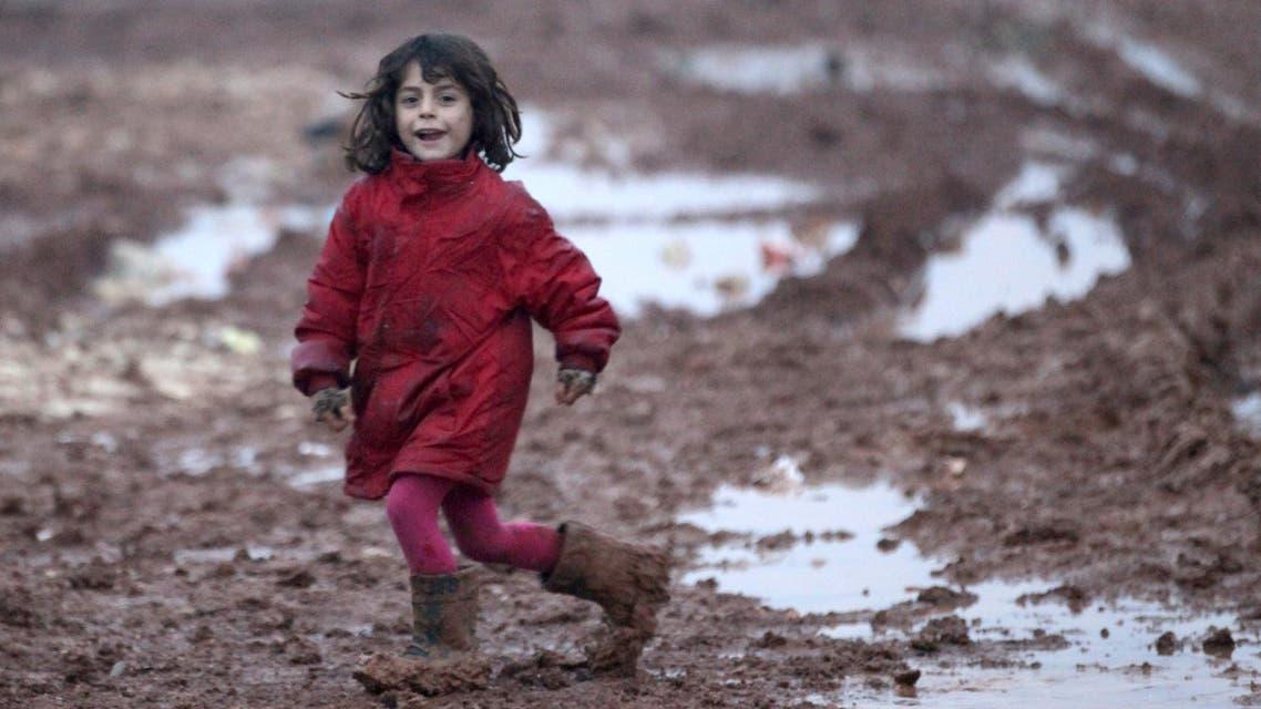 An internally displaced Syrian girl runs through mud in the Bab Al-Salam refugee camp, near the Syrian-Turkish border, northern Aleppo province, Syria December 26, 2016. REUTERS/Khalil Ashawi