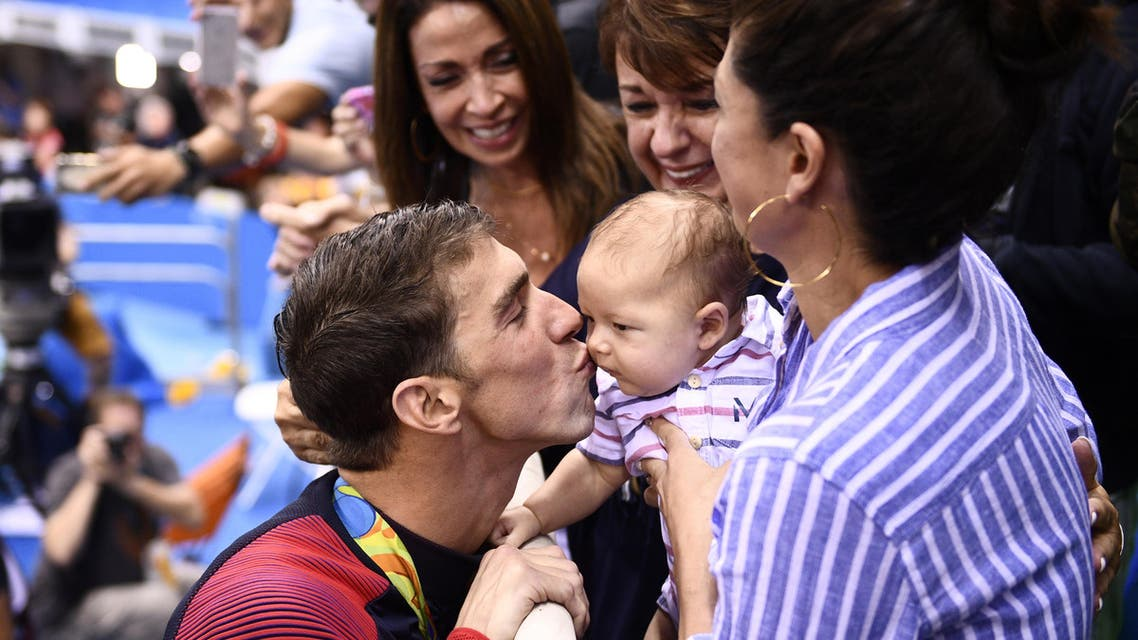 USA's Michael Phelps (L) kisses his son Boomer next to his partner Nicole Johnson (R) and mother Deborah (C) after he won the Men's 200m Butterfly Final during the swimming event at the Rio 2016 Olympic Games at the Olympic Aquatics Stadium in Rio de Janeiro on August 9, 2016. (AFP)