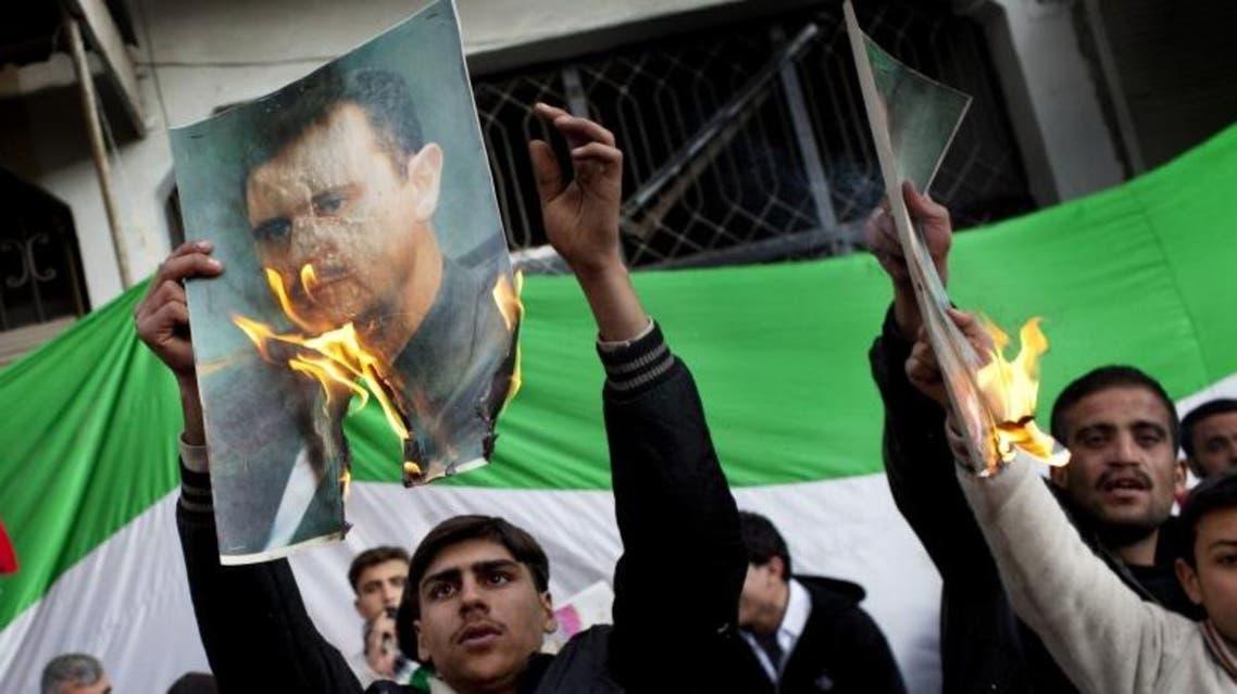 Protestors burn portraits of Syrian President Bashar Assad during an anti-government demonstration (photo credit: AP/Rodrigo Abd)