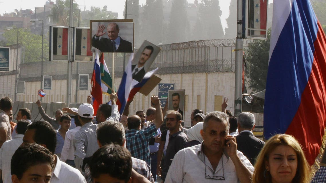 Several hundred people, holding up Russian and Syrian flags as well as portraits of the two countries' presidents, gather near the Russian embassy in Damascus on October 13, 2015 to express their support for Moscow's air war in Syria, just before two rockets struck the embassy compound sparking panic among the crowd. AFP PHOTO/LOUAI BESHARA