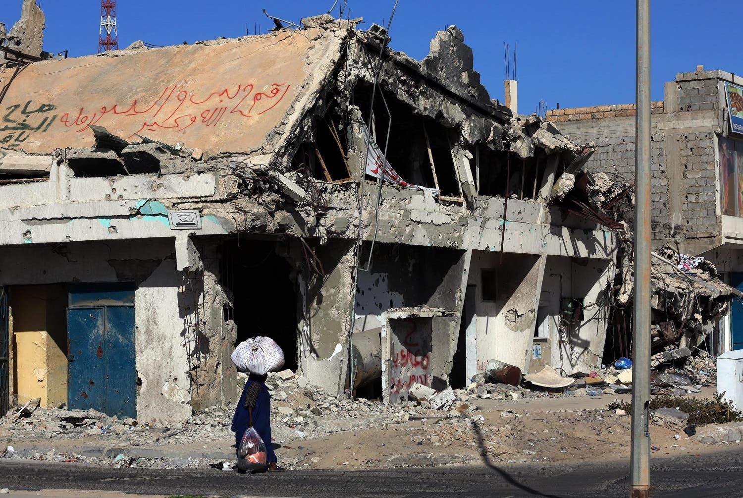 A Libyan woman walks past the rubble of a building in the Mediterranean city of Sirte. (AFP)