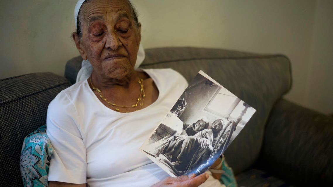 This Monday, July 11, 2016, photo shows Yemen born Jewish Israeli Yona Josef weeping in her home in Raanana, Israel. Josef wept as she clutched an old picture of herself as a child in Yemen and recounted losing her sister. (AP)