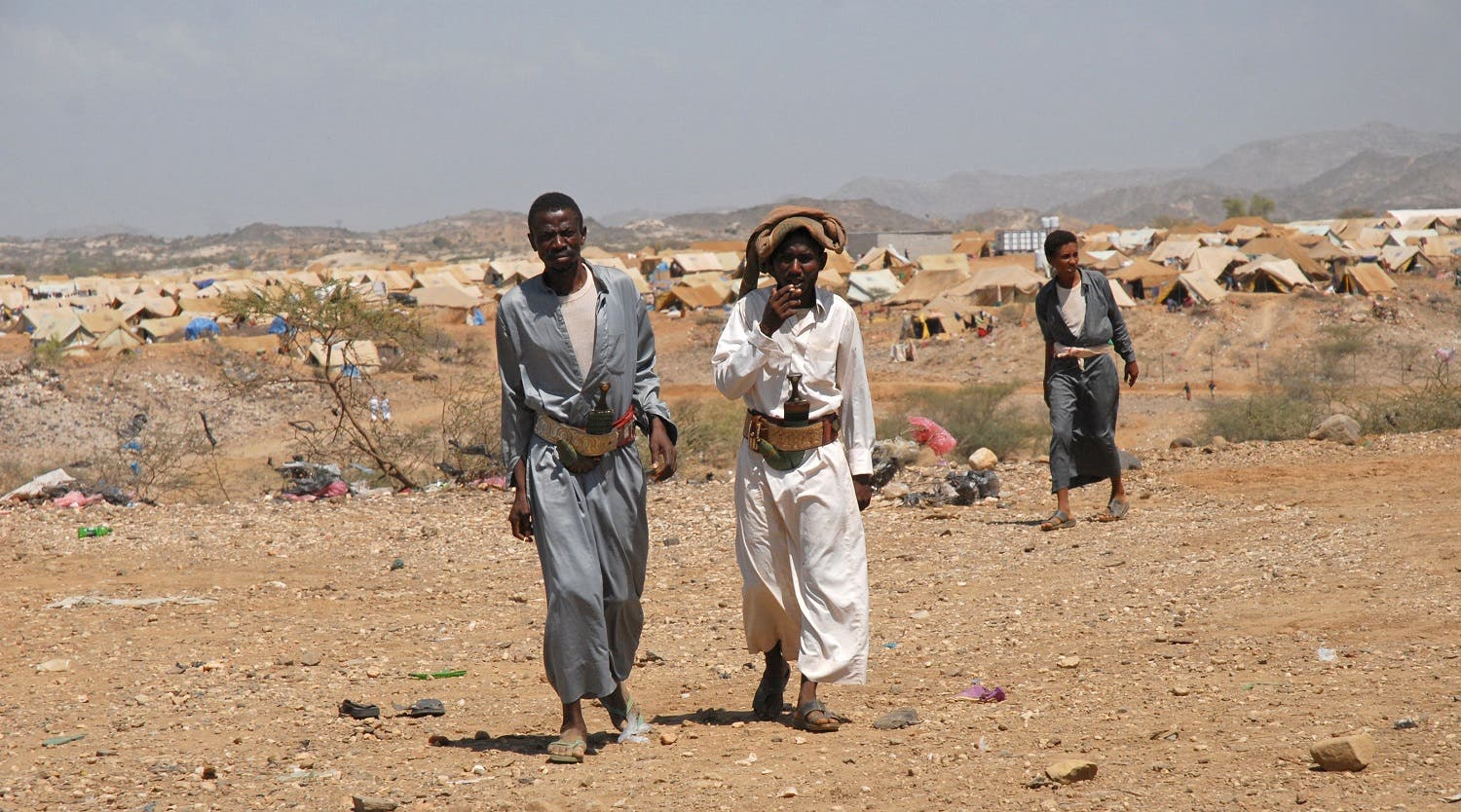 Yemeni men wearing their traditional curved daggers in their belts walk in the grounds of the Mazraq camp set-up for internally displaced Yemenis in the northwestern province of Hajjah.