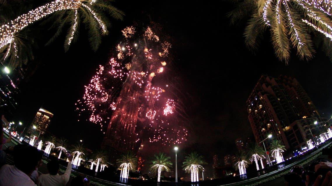Fireworks illuminate the Burj Khalifa as a tower burns behind it in Dubai, United Arab Emirates on Friday, Jan. 1, 2016. (AP)