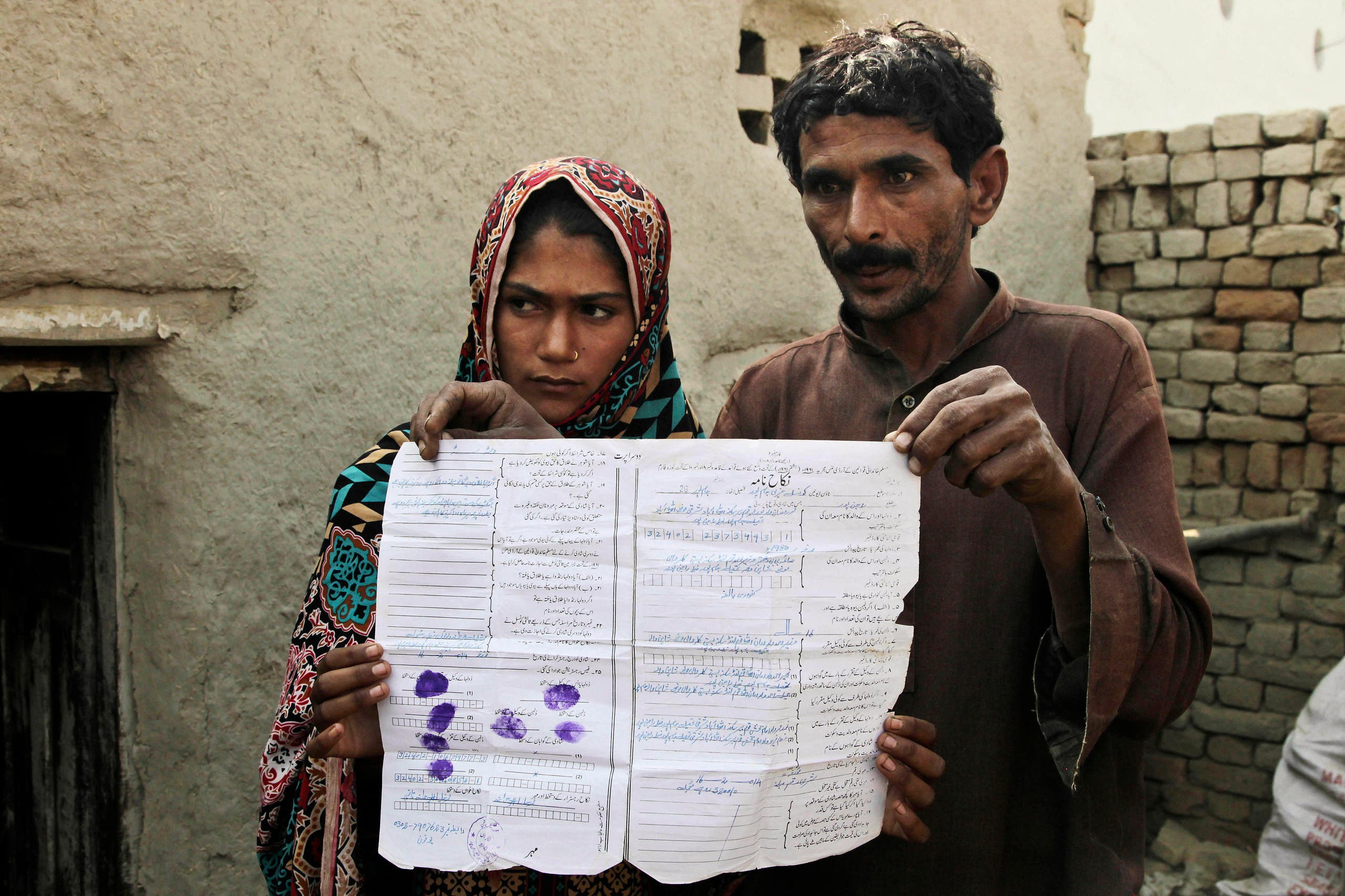 Mohammad Ramzan shows his marriage contract with his young bride Saima in Jampur, Pakistan. (AP)