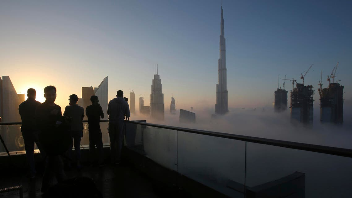 Photographers take pictures as the sun rises over the city skyline with the Burj Khalifa, world's tallest building at the backdrop, seen from a balcony on the 42nd floor of a hotel on a foggy day in Dubai, on Dec. 31, 2016. (AP).