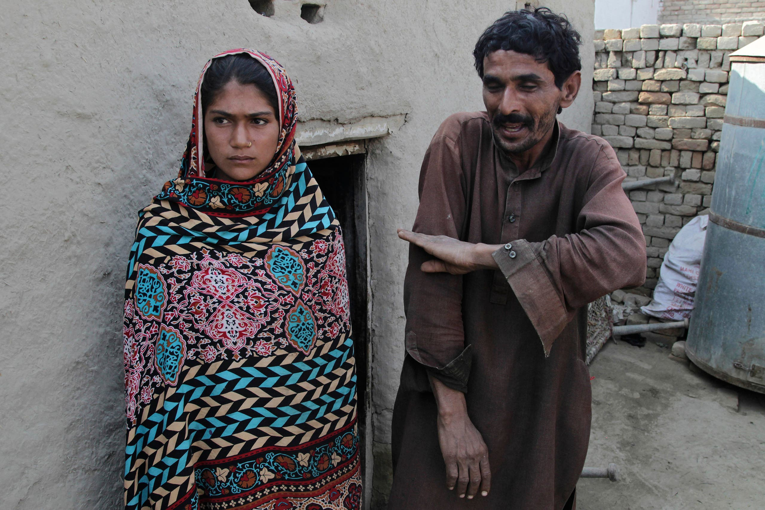 Mohammad Ramzan points out the height of his young bride Saima, left, when she was married to him, in Jampur, Pakistan. (AP)