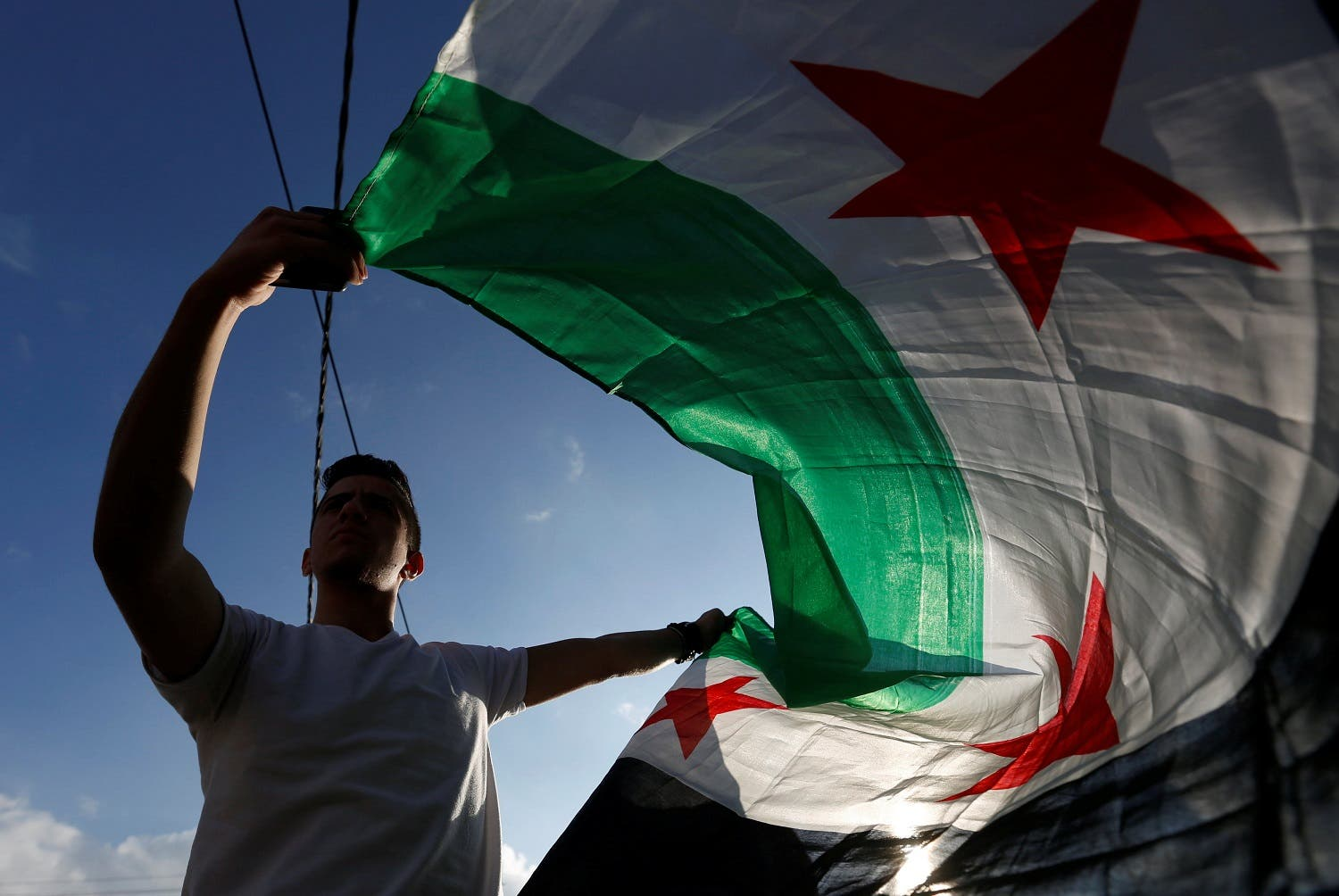 A protester holds a Syrian opposition flag during a sit-in, in solidarity with the people of Aleppo against the Syrian regime in Amman. (Reuters)