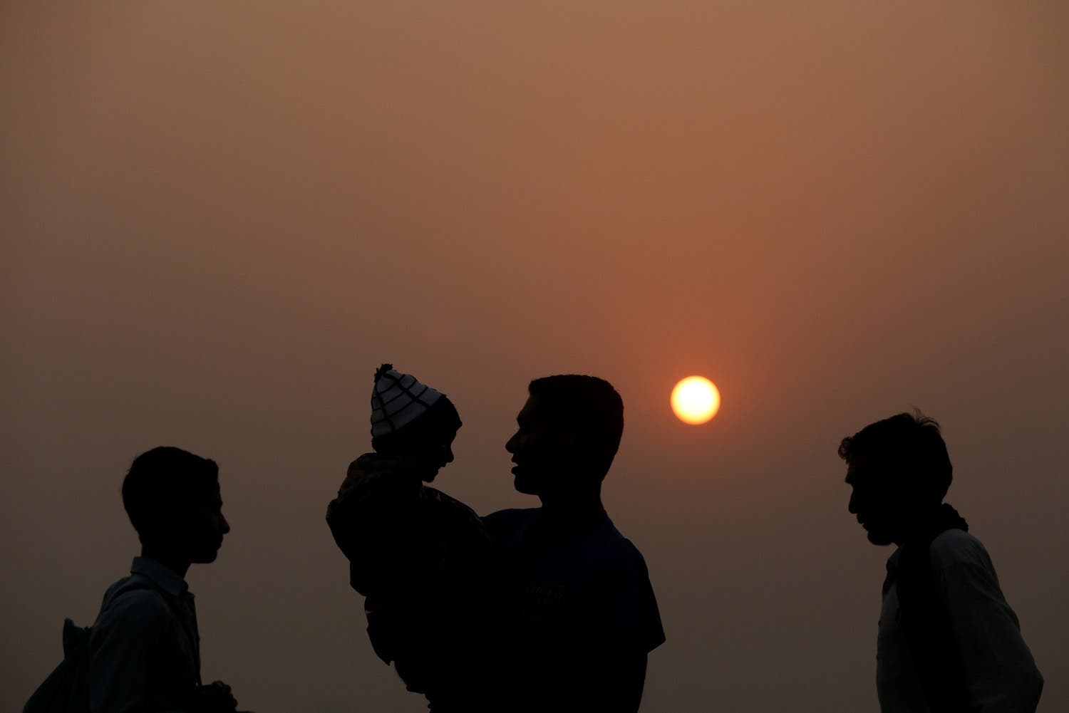 People are silhouetted during the last sunset of 2016 in Karachi. (Reuters)