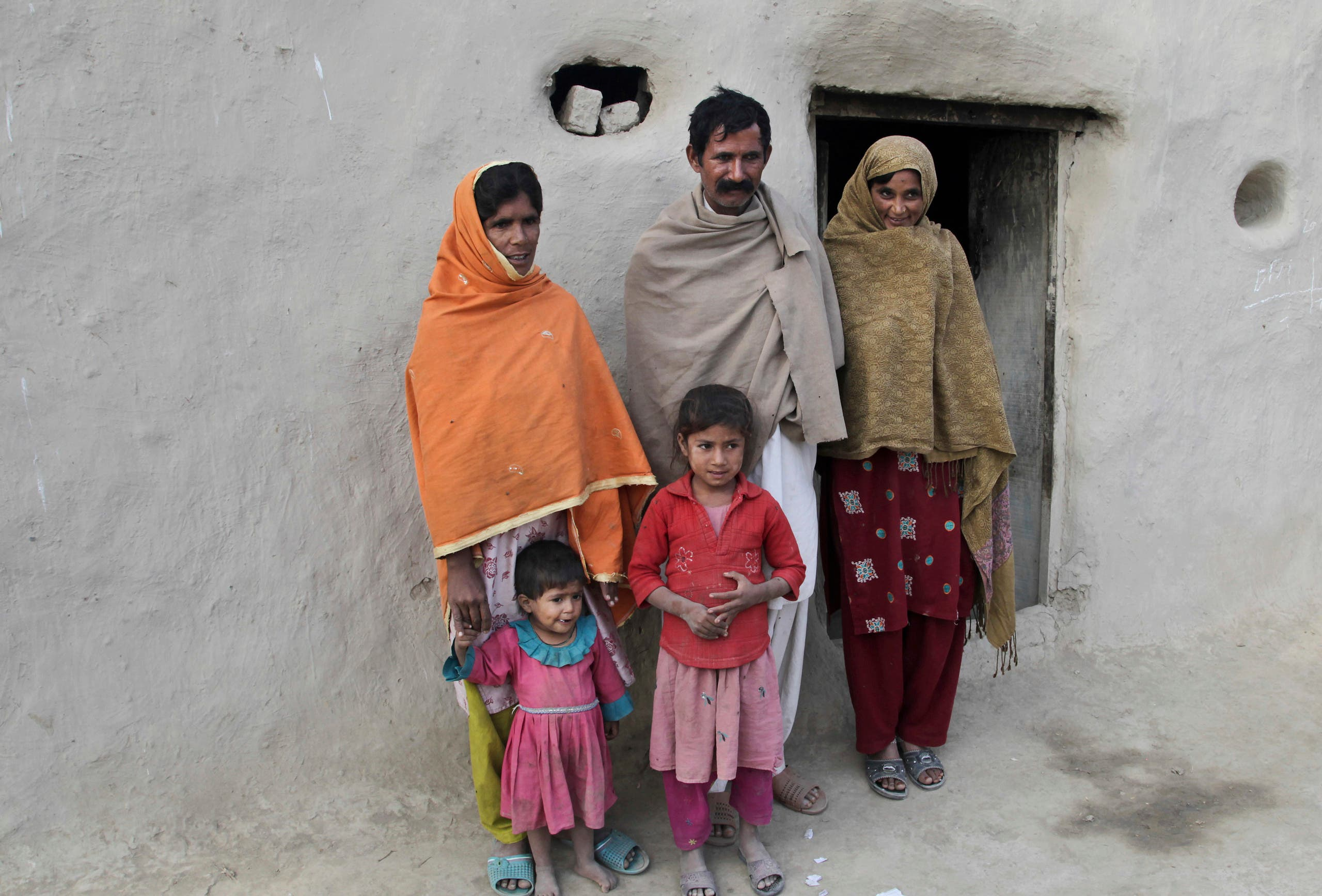 Wazir Ahmed, father of Saima who married Mohammad Ramzan, stands with his wives Sabeel right, and Jannat in Jampur, Pakistan. (AP)