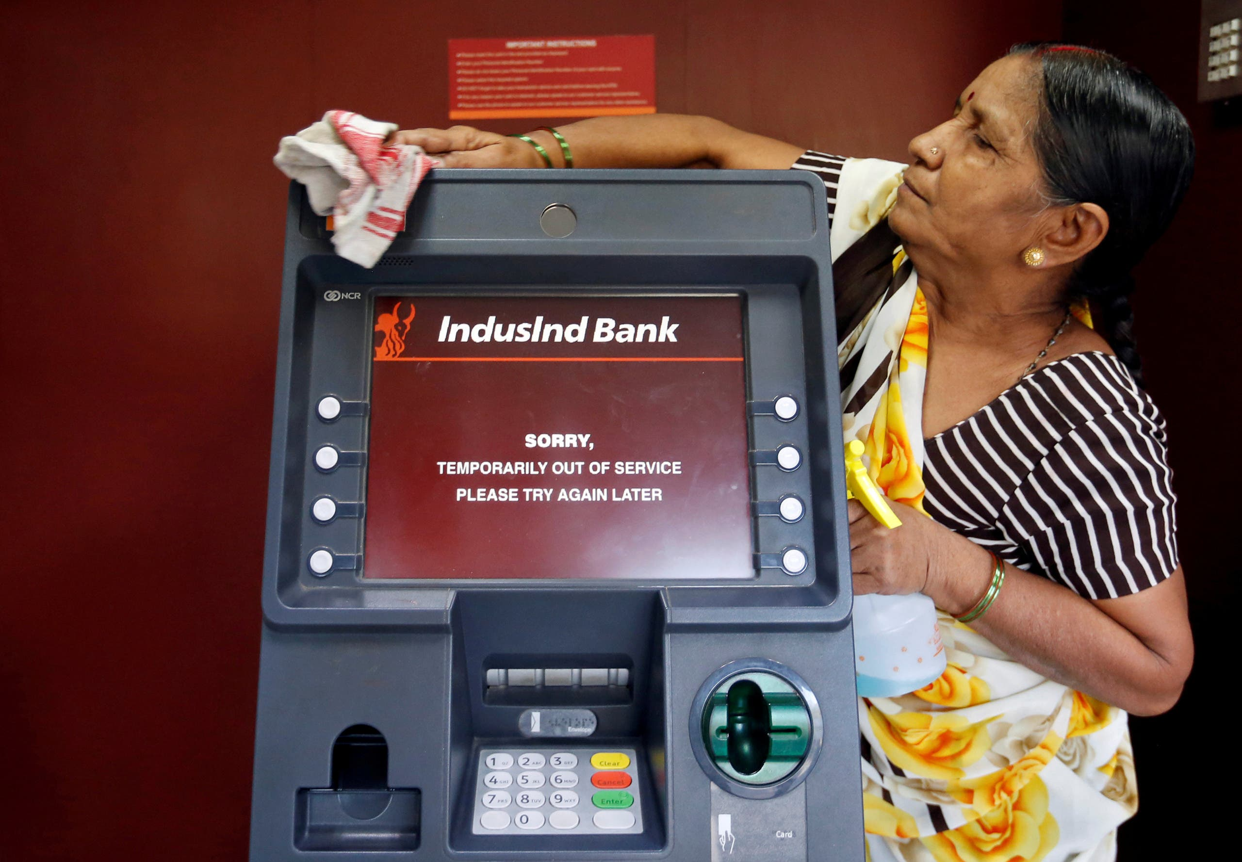 A woman cleans an ATM which is out of service in Mumbai, India, November 11, 2016.(Reuters)
