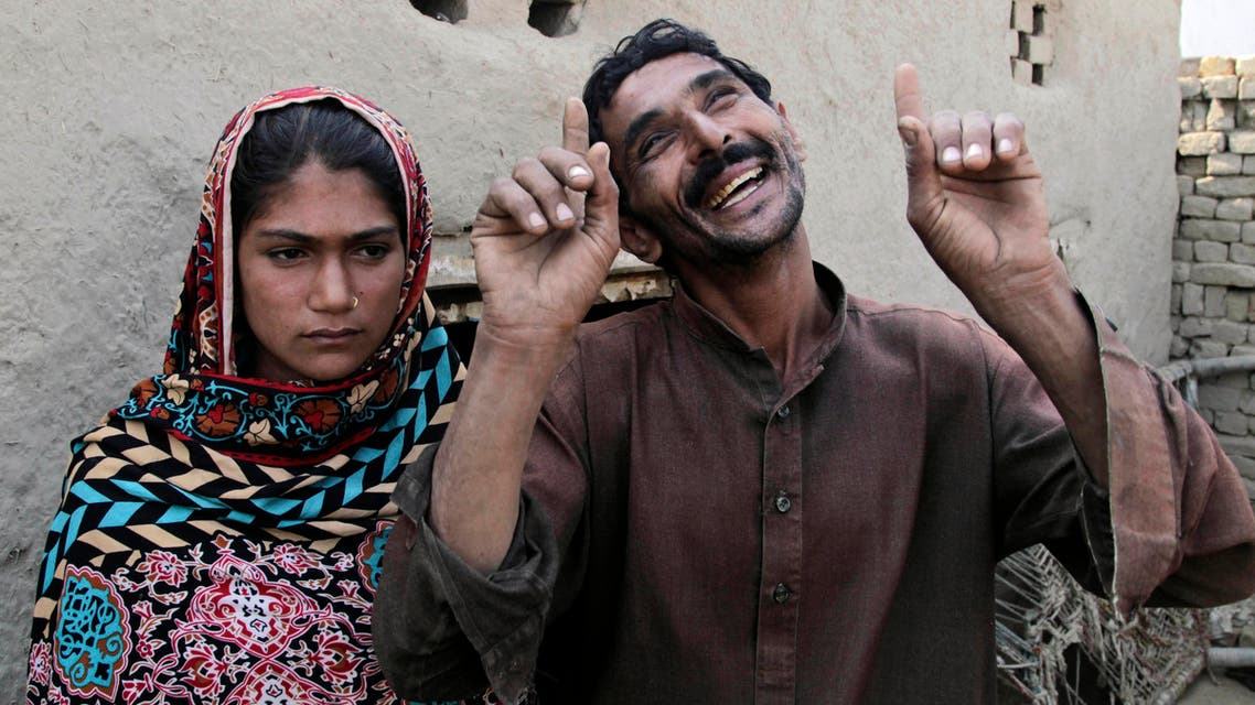 Mohammad Ramzan, right, reacts while talking to The Associated Press with his young bride Saima in Jampur, Pakistan. (AP)