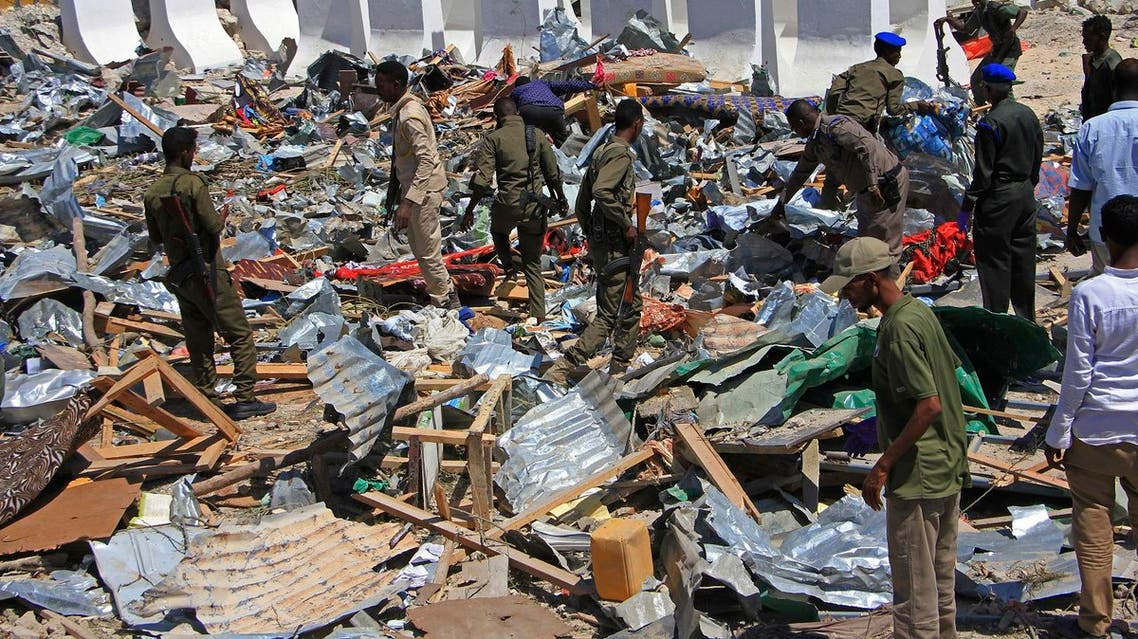 Somali soldiers filter through the debris of a destroyed building near the scene of a suicide car bomb attack in Mogadishu, Somalia, Monday, Jan, 2, 2017. A suicide bomber detonated an explosives-laden vehicle at a security checkpoint near Mogadishu's international airport Monday, killing at least three people, a Somali police officer said. (AP Photo/Farah Abdi Warsameh)
