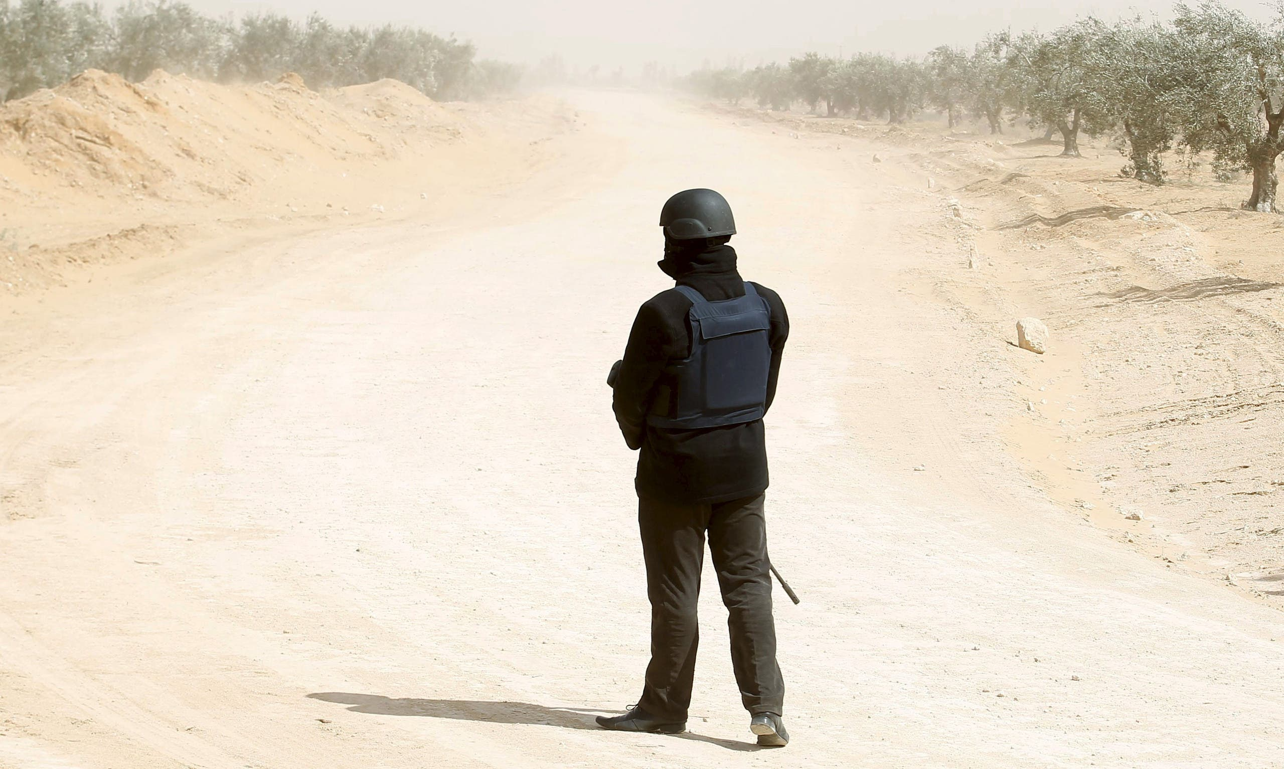 A Tunisian police officer stands guard during an operation to eliminate militants in a village some 50 km (31 miles) from the town of Ben Guerdane, Tunisia, near the Libyan border, March 10, 2016. (Reuters)