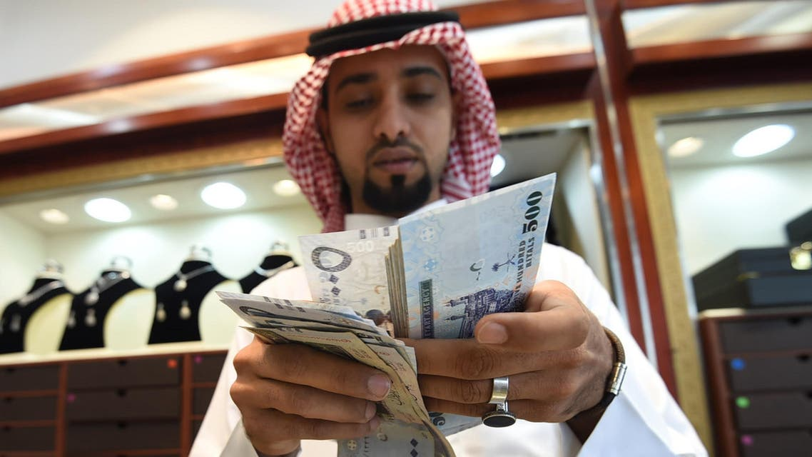 A Saudi man counts banknotes at his jewelry shop at Tiba market in Riyadh, on October 3, 2016. Since 2014 global oil prices have collapsed by more than half, leaving Saudi Arabia with a record deficit last year. The shortfall in the kingdom's main revenue source had already led to unprecedented subsidy cuts and a slowdown in government projects as the administration tries to diversify the economy. FAYEZ NURELDINE / AFP