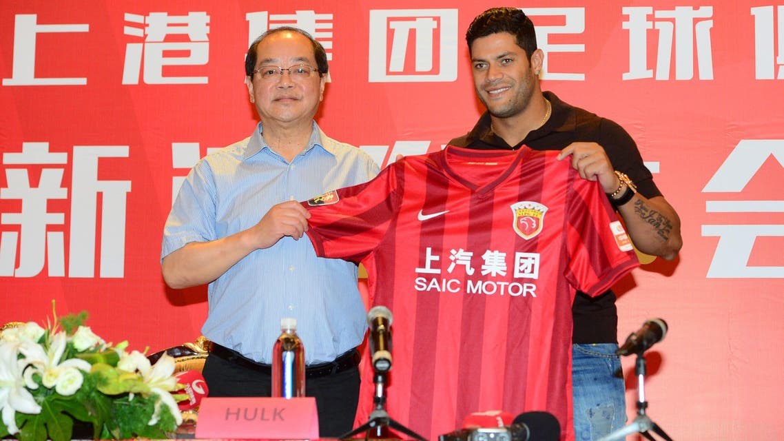 Brazil's Hulk (R) poses with his new jersey during a press conference for joining Shanghai SIPG Football Club in Shanghai on July 1, 2016. Zenit St Petersburg's Brazilian international Hulk arrived in Shanghai on June 29 to sign for Sven-Goran Eriksson's Shanghai SIPG team, as the cash-flush Chinese Super League embarks on a new round of transfer spending. STR / AFP