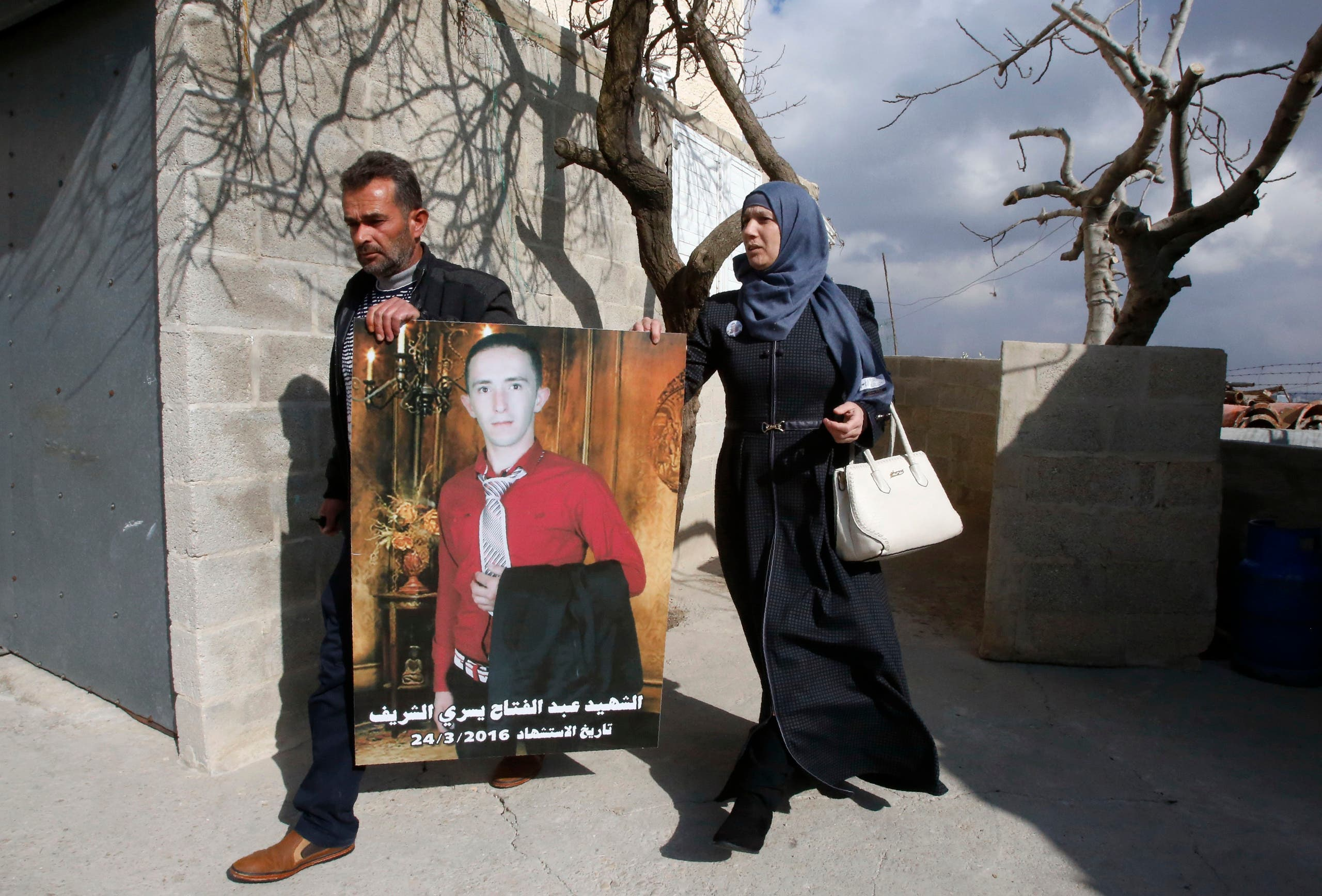 Rajaa and Yousri the mother and father of Abdul Fatah al-Sharif (portrait) head out into the streets in the West Bank town of Hebron on January 4, 2017, after watching on television the verdict of the trial of Israeli soldier Elor Azaria who killed their son. AFP