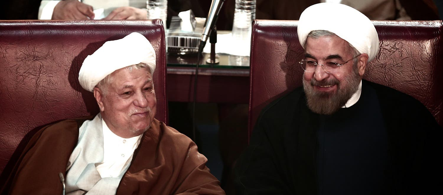 Iranian President Hassan Rowhani (R) chats with former president Akbar Hashemi Rafsanjani during a session of the Assembly of Experts in Tehran on September 3, 2013. (AFP)