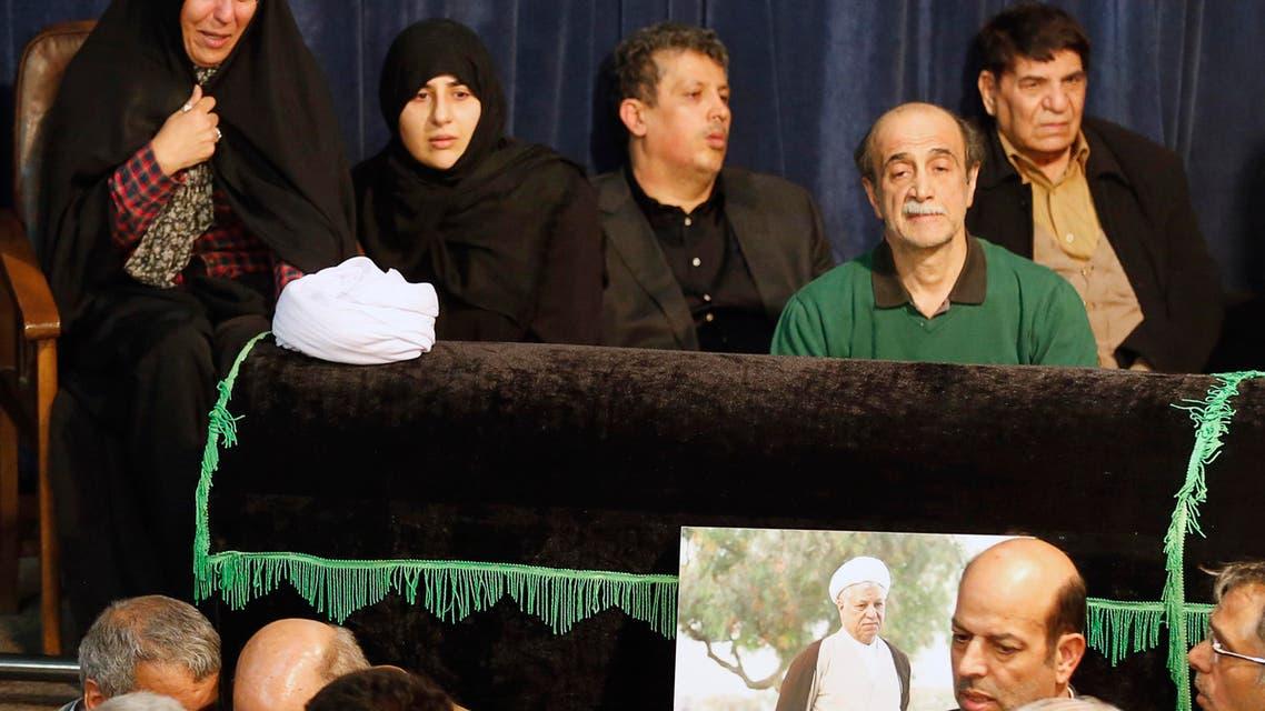 Mehdi Hashemi Rafsanjani (C) and Fatemeh Hashemi Rafsanjani (L), the children of late former Iranian president Akbar Hashemi Rafsanjani, gather with mourners around Rafsanjani's coffin during a mourning ceremony at Jamaran mosque in Tehran, on January 8, 2017. (AFP)