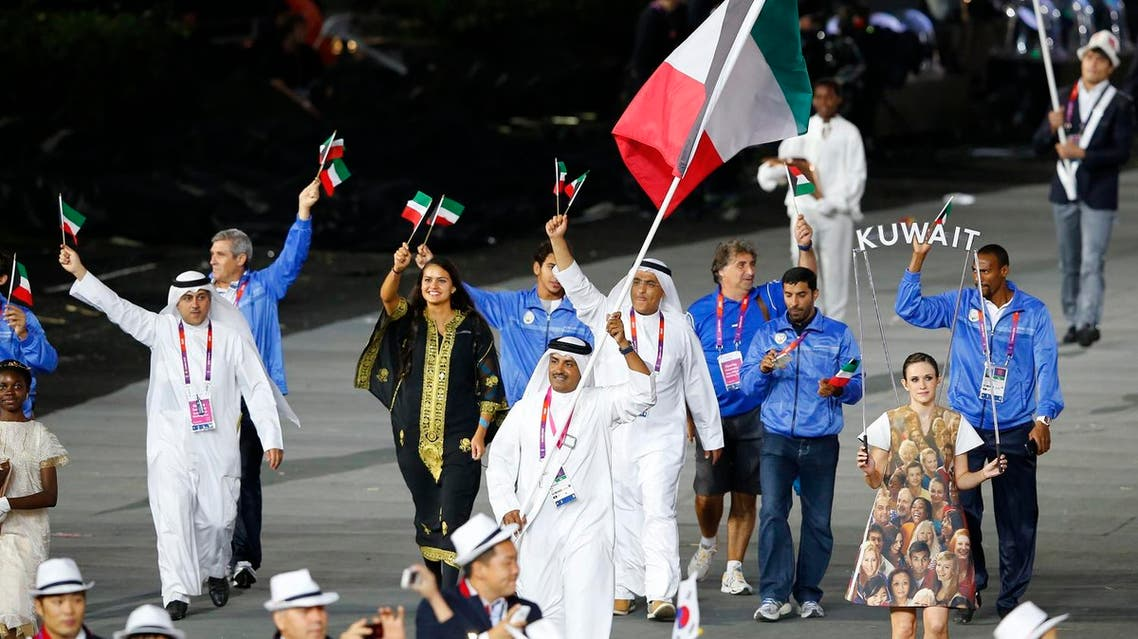 Kuwait's flag bearer Fehaid Aldeehani holds the national flag as he leads the contingent in the athletes parade during the opening ceremony of the London 2012 Olympic Games at the Olympic Stadium July 27, 2012. (AFP)
