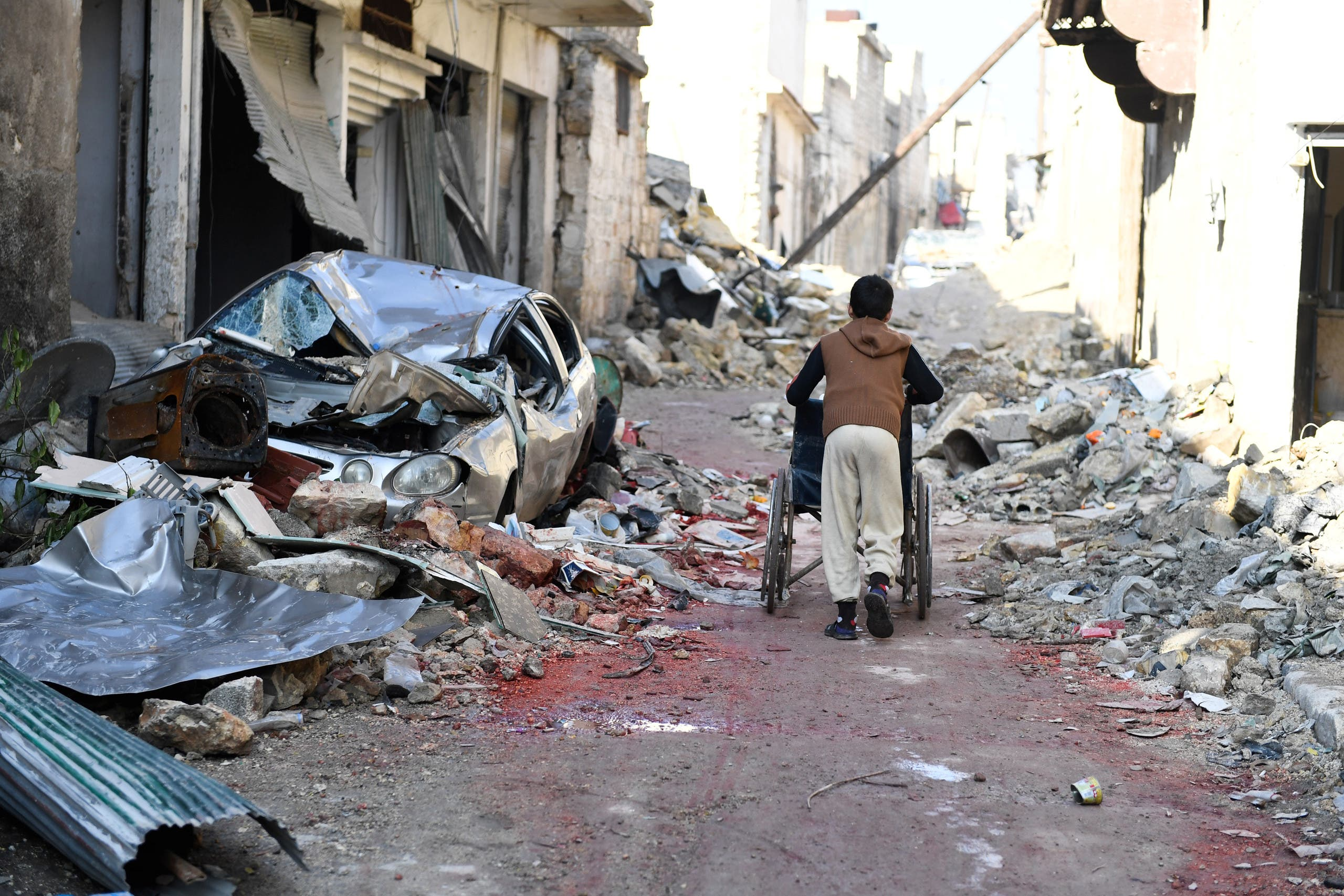 A boy pushes a wheelchair along a damaged street in the east Aleppo neighborhood of al-Mashatiyeh, Syria, in this handout picture provided by UNHCR on January 4, 2017. Bassam Diab/UNHCR/Handout via REUTERS ATTENTION EDITORS - THIS PICTURE WAS PROVIDED BY A THIRD PARTY. REUTERS IS UNABLE TO INDEPENDENTLY VERIFY THE AUTHENTICITY, CONTENT, LOCATION OR DATE OF THIS IMAGE. FOR EDITORIAL USE ONLY.