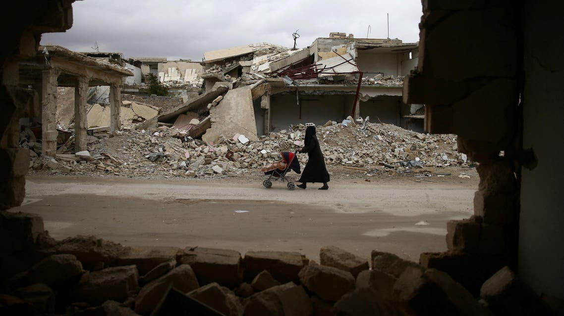 A woman pushes a baby trolley past damaged buildings in the rebel held besieged city of Douma, in the eastern Damascus suburb of Ghouta, Syria January 8, 2017. REUTERS/Bassam Khabieh TPX IMAGES OF THE DAY