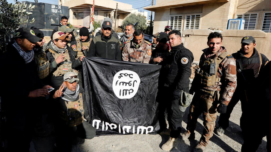 Lieutenant General Abdelwahab al-Saadi (C) and members of Iraqi Counter Terrorism Forces hold an Islamic State flag which they pulled down during a battle with Islamic State militants, east of Mosul, Iraq, January 11, 2017. REUTERS/Ahmed Saad